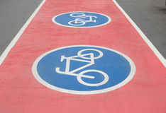 Знак велосипеда на красном путе велосипеда Стоковые Фотографии RF