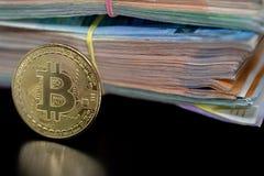 Знак внимания Bitcoin на черноте с отражением, с большой кучей денег банкноты евро на заднем плане стоковые изображения rf