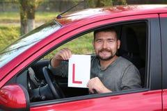 Знак водителя учащийся показа человека от нового автомобиля стоковая фотография