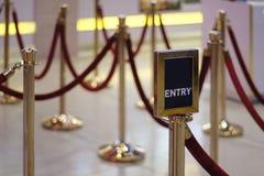 Знак входа/выхода против барьера веревочки очереди опоры барьера веревочки вывешивает сдерживание толпы стоек стоковые фото