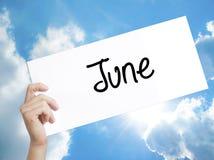 Знак в июне на белой бумаге Рука человека держа бумажной с текстом Iso стоковое фото rf