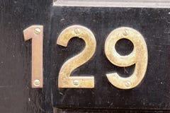 Знак дома 129 на двери Стоковая Фотография