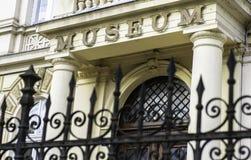 Знак и вход музея в сфокусированную предпосылку, железную загородку Стоковая Фотография