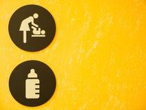 Знак и символ раздевалки младенца с желтой предпосылкой Стоковое Изображение RF