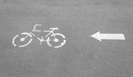 Знак и стрелка майны велосипеда на конкретной дороге Стоковое Изображение