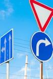 Знак который показывает дорогу и поворот только справедливо к предпосылке гениального голубого неба стоковое фото