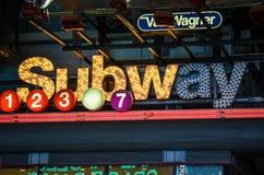 Знак метро Нью-Йорка освещенный вверх на ноче Стоковые Фотографии RF