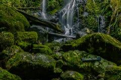 Знак на валуне около водопада стоковые изображения