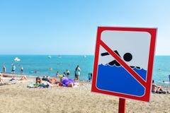 Знак на пляже не позволен поплавать! Люди купают и отдыхают на море несмотря на знак и запрет стоковое изображение rf