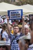 Знак нося молодого человека на марте для нашего вооруженного насилия Prot жизней Стоковое фото RF