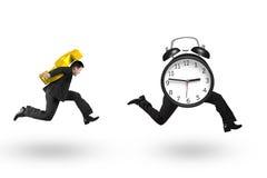 Знак нося доллара человека бежать после будильника Стоковые Фотографии RF