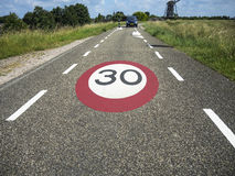 Знак ограничения в скорости на дороге Стоковая Фотография