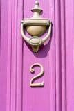 Знак дома 2 на розовой двери цвета с латунным knocker двери Стоковая Фотография RF