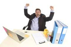 Знак победы молодого привлекательного бизнесмена шальной счастливый делая сидя на праздновать стола компьютера офиса Стоковая Фотография RF