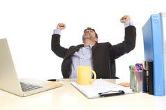 Знак победы привлекательного бизнесмена шальной счастливый делая сидя на праздновать стола компьютера офиса Стоковые Изображения RF