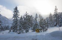 Знак поворота над смещением снега на дорогу горы стоковые фотографии rf