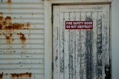 Знак пожарной безопасности на двери древесины характеристики стоковые изображения