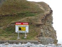 Знак показывая опасные скалы на Pebble Beach в Великобритании стоковое изображение