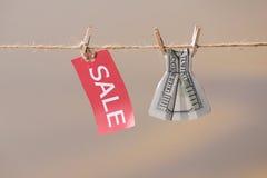 Знак продажи и 100 банкнот доллара США на веревке для белья Стоковое Изображение
