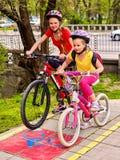 Знак пути велосипеда с детьми Девушки нося шлем с рюкзаком Стоковые Фотографии RF