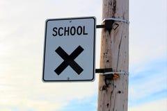 Знак скрещивания школы на опоре линии электропередач с предпосылкой облачного неба Стоковые Фотографии RF