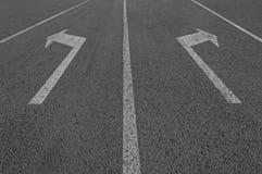 Знак стрелок на дороге асфальта Стоковое Фото