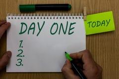 Знак текста показывая день одно Схематическое начало первого шага момента начала фото удерживания человека события программы расп стоковые изображения
