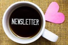 Знак текста показывая информационый бюллетень Схематический бюллетень фото периодически посылаемый к подписанной кофейной чашке в стоковые фотографии rf