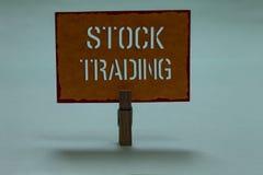Знак текста показывая торговлю акциями Схематические покупка фото и надувательство безопасностей электронно на holdi зажимки для  стоковое фото