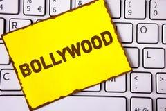 Знак текста показывая Bollywood Кино схематического фото индийское источник развлечений написанный на желтой липкой бумаге примеч Стоковые Фотографии RF