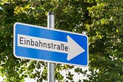 Знак улицы пути немца одного с деревьями на заднем плане Стоковая Фотография RF