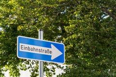 Знак улицы пути немца одного с деревьями на заднем плане Стоковое фото RF