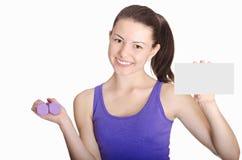 Знак чистого листа бумаги счастливого показа девушки фитнеса усмехаясь пустой Стоковое Изображение RF
