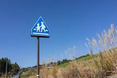 Знак школы, дети пересекая знак около улицы с ясностью Стоковая Фотография