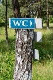 Знак WC пригвозженный к дереву Стоковое фото RF