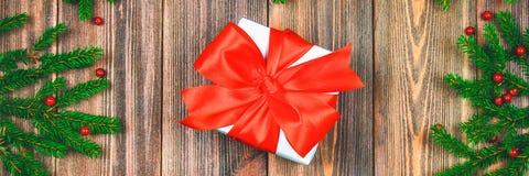 знамена Елевые ветви с красными ягодами на деревянном столе В центре коробки с настоящими моментами перевязанные смычки Рождество стоковые фото