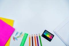 Знамена подпирают к учебникам рисуют запись неподвижной тетради белой предпосылки белая доска стоковые фото