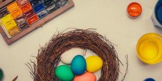 знамена Счастливая пасха! Друзья крася пасхальные яйца на таблице Стоковая Фотография
