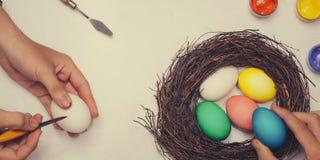 знамена Счастливая пасха! Друзья крася пасхальные яйца на таблице Стоковые Изображения