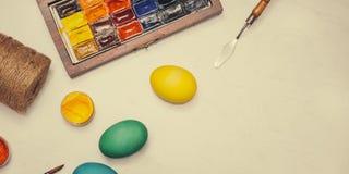 знамена Счастливая пасха! Друзья крася пасхальные яйца на таблице Стоковое Фото