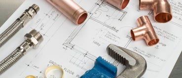 Знамя инструментов водопроводчиков и материалов трубопровода на планах дома Стоковая Фотография