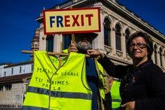 Знамя, который держит французское Gilet Jaunes, желтое движение жилета, протестующие вызывая для Frexit, французский выход, на фр стоковое фото