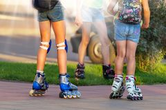 Знамя маленьких ребят ехать коньки ролика в городе закройте вверх по ногам стоковые фото