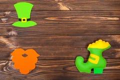 Знамя темы дня ` s St. Patrick красочное горизонтальное Зеленые шляпа, борода и ботинок лепрекона с золотом на коричневой деревян Стоковое фото RF