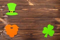 Знамя темы дня ` s St. Patrick красочное горизонтальное Зеленые шляпа лепрекона, борода и листья shamrock на коричневой деревянно Стоковые Фото