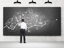 Значки и диаграммы чертежа бизнесмена startup Стоковое Изображение