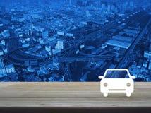 Значок автомобиля плоский на деревянном столе над антенной современной башни города, Стоковые Фотографии RF