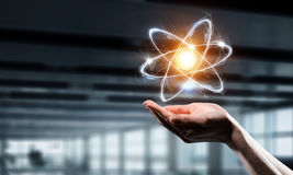 Значок атома в ладони Мультимедиа Стоковые Изображения RF