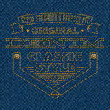 Значок вышитый на голубой предпосылке текстуры джинсовой ткани Стоковое Фото