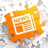 Значок газеты с словом новостей на оранжевой головоломке. Стоковые Изображения